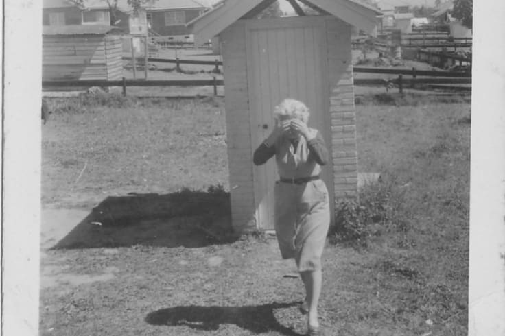 A woman leaving a Coopers Plains dunny, nursing a headache.