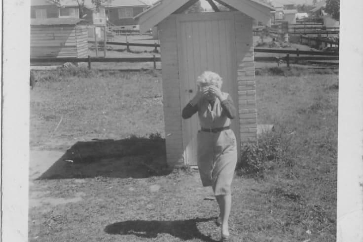A woman leaving a Coopers Plains dunny, nursing a headache.