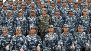 El presidente chino, Xi Jinping (centro con uniforme militar verde) posa con soldados en un barco de la Armada en 2018.