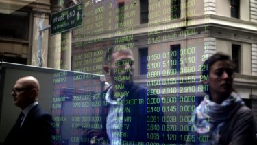 A reflection of passersby and the ASX stock board on Bridge Street in Sydney. generic stock exchange ASX  investor shares portfolio
