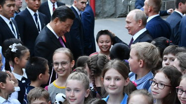 Chinese President Xi Jinping, centre left, and Russian President Vladimir Putin, centre right, at the Moscow Zoo with school children to mark the handover of two pandas to Moscow.