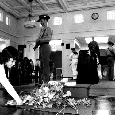 Zoe Sander lays a flower at the coffin of the unknown soldier in Kings Hall at Old Parliament House.