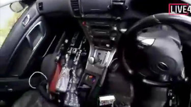 A screenshot from the alleged gunman's video showing the high-powered weapons used in the attack on his front passenger seat.