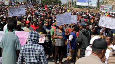 Papuans hold posters during a protest in Timika, Papua province.