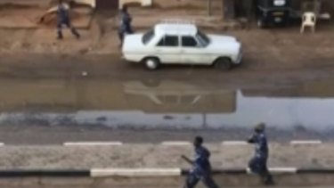 Police officers run down a street in Khartoum, Sudan, on Monday.