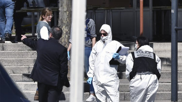 Police officers investigate on Saturday after a Sudanese man wielding a knife attacked residents of Romans-sur-Isere who were out shopping in the town under lockdown.