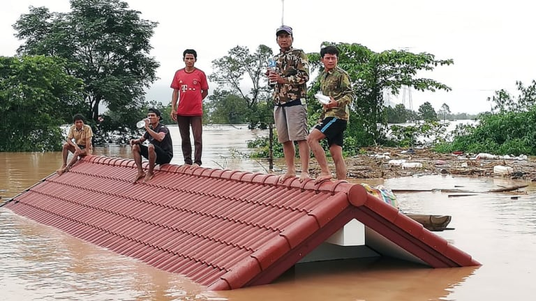 Floods are an international problem: Laotians villagers stranded on a roof of a house due to floodwaters after a dam collapsed.
