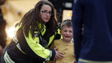 Officials guide students off a bus to be reunited with their parents after a shooting at a suburban Denver school.