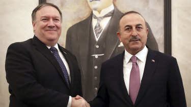 Turkey's Foreign Minister Mevlut Cavusoglu, right, and US Secretary of State Mike Pompeo shake hands before a meeting at the Esenboga Airport in Ankara, Turkey.