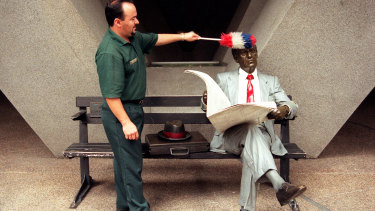"A cleaner dusts off Seward Johnson's ""Waiting"" at Australia Square in Sydney."