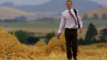 Rural doctor Nathan Grills walks through a paddock of stacks of sheaf hay in the Ascot area north  of Ballarat.