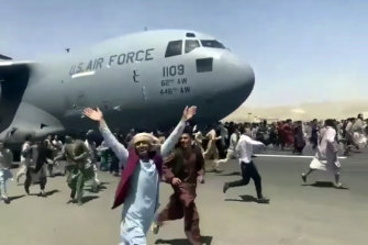 Chaos on the tarmac: hundreds of people run alongside a US Air Force C-17 transport plane as it moves down a runway in Kabul after the city fell to the Taliban.