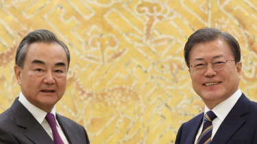 South Korean President Moon Jae-in, right, poses with Chinese Foreign Minister Wang Yi for a photo before a meeting at the presidential Blue House in Seoul.