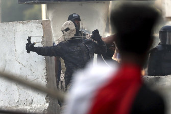 A masked policeman uses a slingshot to fire a stone at demonstrators.