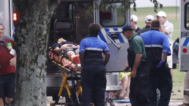 Felled: An injured golf fan is loaded into an ambulance after being struck by lightning near the practice range.