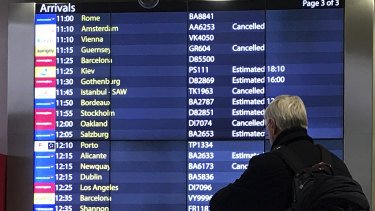 A passenger checks an arrivals board at Gatwick Airport. Flights had returned to normal by Sunday.