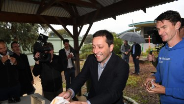 Victorian Opposition Leader Matthew Guy gets a sausage on the final day of the Victorian election campaign, in Melbourne.