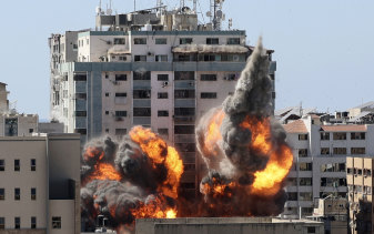 A ball of fire erupts from the media building in Gaza City after an Israeli airstrike.