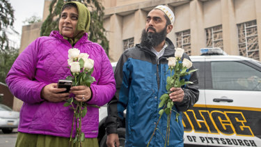 Samina Mohamedali, left, and her husband Kutub Ganiwalla, members of the Dawoodi Bohra Muslim community, both of North Hills, prepare to place flowers on a memorial in front of the Tree of Life Congregation on Sunday.