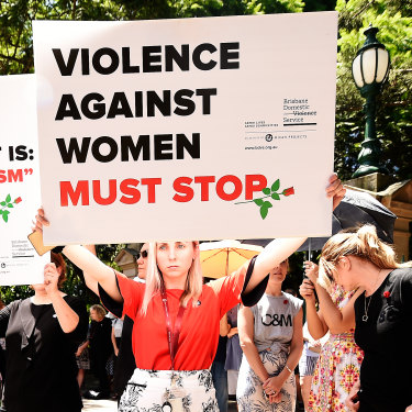 Protesters hold placards during a domestic violence protest organised by the Red Rose Foundation in Brisbane on Friday.
