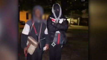 Two of the teenagers pose with the stolen goods before being arrested by police.