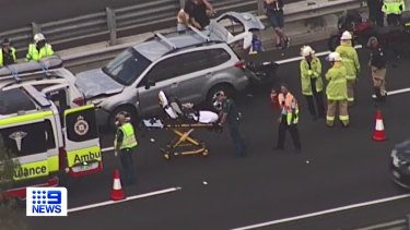 Emergency services swarm the scene on the M1 at Springwood on Monday.
