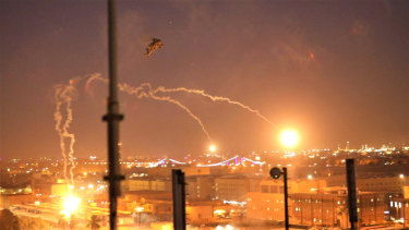 A US army Apache helicopter launches flares as a show of presence while conducting flights over the US Embassy in Baghdad, Iraq.