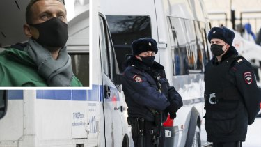 Police officers stand at an entrance of the police station during the Alexei Navalny (inset) court hearing on Monday.