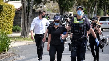 A woman is led away by police in Elsternwick