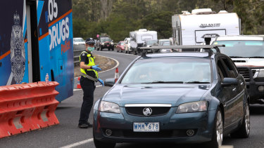 Police stop motorists at acheckpoint in Genoa as they enter Victoria from NSW.