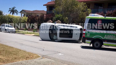 Fremantle forward Jesse Hogan climbed from his car after it flipped after a crash in Bicton on Sunday.