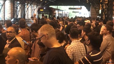 Commuters queued at the light rail stop at Central Station due to wet weather.