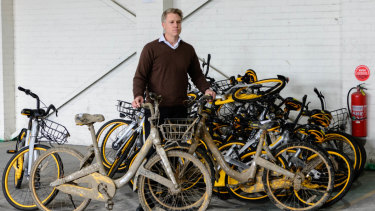 City of Melbourne deputy mayor Arron Wood standing with impounded oBikes.