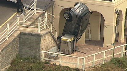 Car crashes through guard rail, lands on pedestrian walkway at Bondi