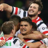 The power of one: Latrell Mitchell (centre) is mobbed by teammates after the final play.