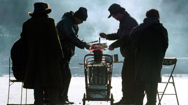 Customers brave clouds of smoke to buy lamb skewers from a vendor with a mobile stall on the ice of a frozen lake in Beijing.