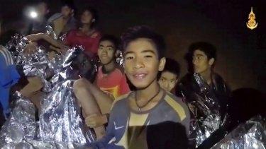 The Thai boys smile as a Thai Navy SEAL medic helps injured teens.