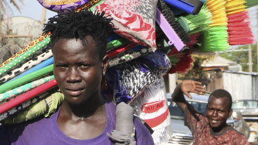 A young merchant carrying brooms to sell walks along a street after the recent ousting of Sudan's President Omar al-Bashir, in the capital Juba, South Sudan.