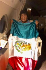Bolivia's former president Evo Morales holding a Mexican flag aboard a Mexican Air Force aircraft as he flees after resigning.