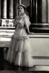 The Queen Mother photographed by Cecil Beaton in a Norman Hartnell gown in the Music Room of Buckingham Palace in 1939.