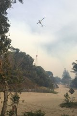A helicopter drops water on the blaze near Happy Valley on Monday.