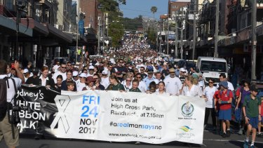 Thousands of people make their way down Coogee Bay Road as part of Sydney's annual White Ribbon walk in 2017.