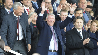 He's back: Former Manchester United manager Alex Ferguson waves as he takes his seat at Old Trafford.