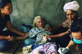 Yayasan Team Action Amed volunteers deliver aid and food packages to an elderly woman.