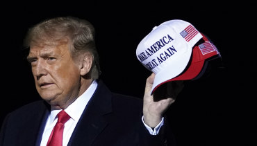 Again? Donald Trump armed with Make America Great Again hats, which he threw to supporters after speaking at a campaign rally in Minnesota on Wednesday.