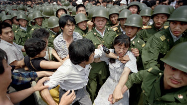 A woman is caught between civilians and Chinese soldiers, who were trying to remove her from an assembly near the Great Hall of the People in Beijing, on June 3, 1989.