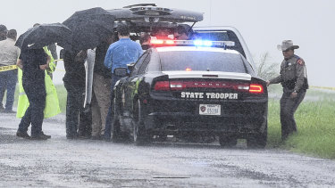 Law enforcement officers gather near the scene where the body of a woman was found near Interstate 35 north of Laredo, Texas on Saturday.