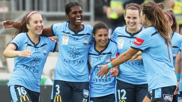 Sydney FC celebrate their route after Shadeene Evans (second left) scores their third in injury time.