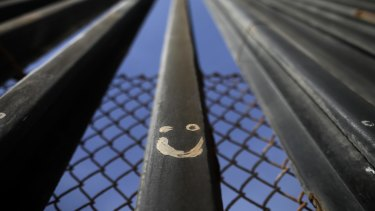 Graffiti adorns metal bars marking the United States border where it meets the Pacific Ocean.