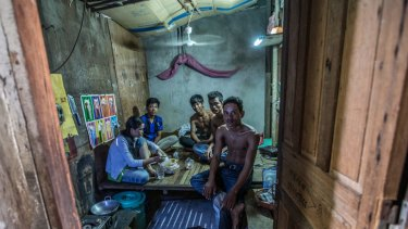 Oem Mom, 33, (woman pictured) sleeps on a wooden bench with four other family members in a tiny room made of scrap timber and cardboard off a dank alleyway near the Phnom Penh factory  in Cambodia.